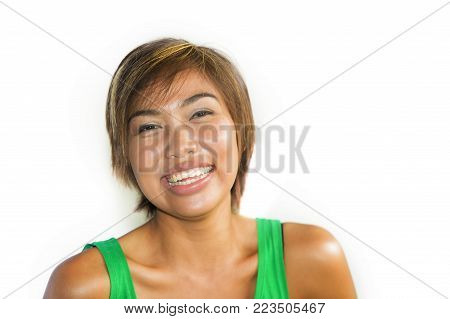 head and shoulders portrait of young beautiful and happy Asian Singaporean or Malay woman smiling joyful and pretty isolated on white background in happiness and fun expression