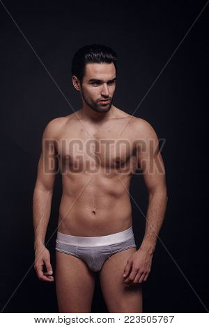handsome man, fasion model, posing in jeans, black background, shirtless, looking at camera.