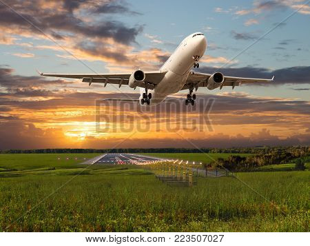 Passenger plane takes off from the airport runway. Aircraft fly during the sunset. Airplane front view.
