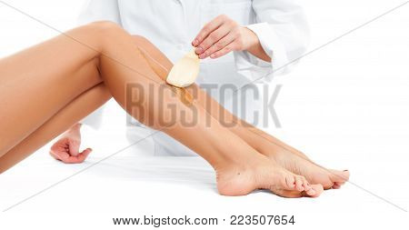 Beauty Spa. Hair removal cosmetology procedure. Beautician waxing a female leg applying a strip of material over the hot wax