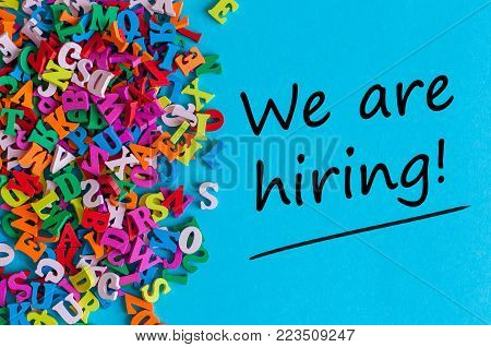 Job recruiting advertisement represented by WE ARE HIRING texts on the blue background. Many color little letters.
