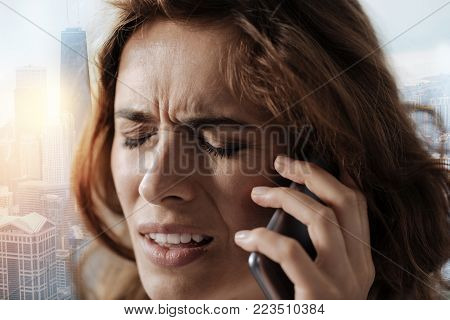 Cant believe it. Portrait of an unhappy woman talking on smart phone while having an unpleasant conversation