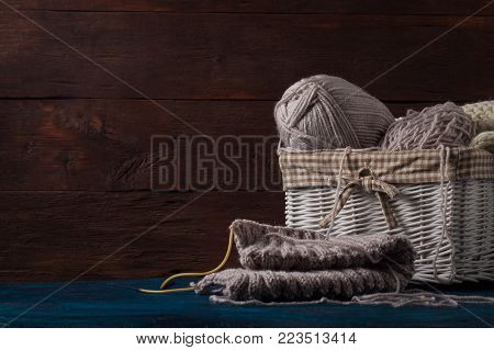 Light Gray Knitting In A Basket And Knitting Needles, A White Knitted Scarf On A Wooden Background.