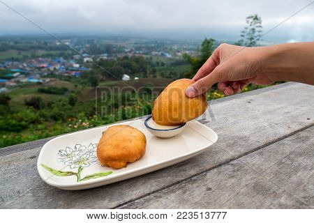 Fried steamed bun was dip in the sweetened condensed milk in a bowl with mountain village background, Traveling in Thailand