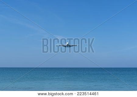 An airplane landing to the airport over the blue sea