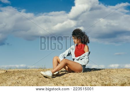 young girl sitting on the sand in profile against the sky , a young woman breathing fresh air.