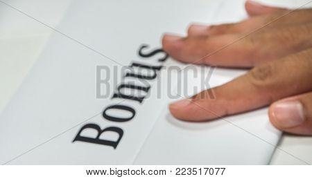 Company bonus concept - close up blurred and defocused annual bonus with boss hand