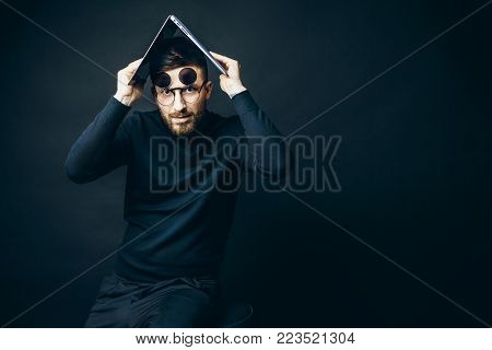 Bearded man in flip-up glasses looking at camera holding laptop above head on black background.