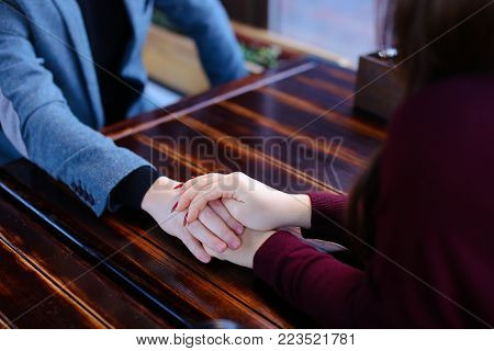 Bride and groom holding hands discuss wedding and honeymoon in Paris in coffee house, lovers on date in cozy cafe. Male in blue jacket and female in burgundy dress sitting near wooden table. Concept of journeys for lovers or event planning, luncheonette w