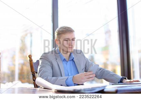 Young businessman sitting at cafe table and checking project. Blonde man wearing smart watch. Concept of modern gadgets and architecture drafting roll.