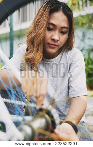 Vietnamese female cyclist fixing chain on her bike