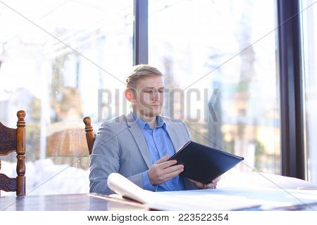 Construction company manager sitting at cafe, resting with drafting project and black document cases on table. Young man dressed in classic suit relaxing. Concept of architectural drawing and catering establishment.