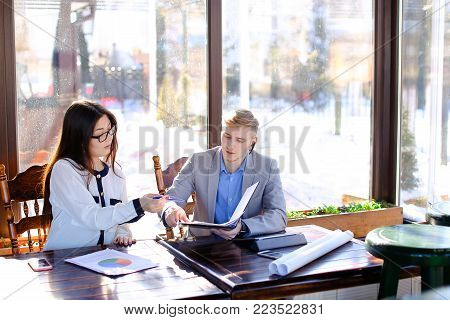 Sales manager talking with client by hands free phone and working at cafe with female secretary. Young girl in glasses reading document papers. Concept of commercial business and catering establishment.