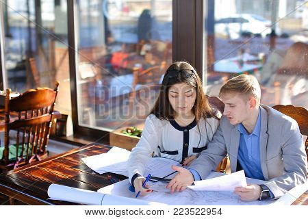 Students of architectural faculty calling to teacher to ask about architectural project. Guy and girl drafting at cafe. Concept of work in pair and drawing course work.