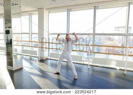 Male barefoot dancer jumping into somersault . Young person training at studio with large mirrors. Concept of persistence and hard practice for success in dancing career.