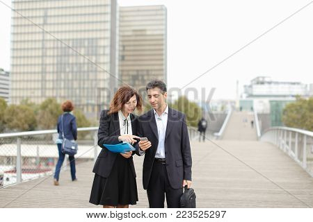 Middle-aged business man and woman classmates long time ago, accidentally met on street. Male show Female photo of family on smartphone and tell about wife with children. Female hold blue folder with paper, enthusiastically listen and smile.