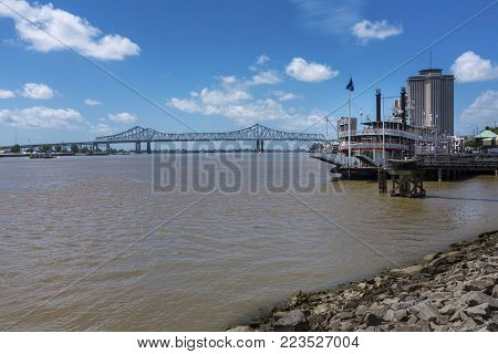 New Orleans, Louisiana - June 17, 2014: View of the Mississippi river from the city of New Orleans riverfront, with a Mississippi Steamboat and the Great New Orleans Bridge on the background in New Orleans, Louisiana.