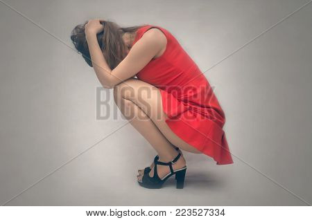 Desperation. The girl is under stress. Tired and sad woman in depression girl kneels on the floor and clasps her head with her hands. Melancholy concept.