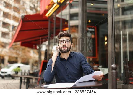 Real estate agent talking with disgruntled client by smartphone at cafe table in  .  Annoyed Caucasian man wears classic style clothes. Concept of salesperson as intermediary between sellers and buyers.