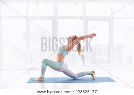 Beautiful young woman practices yoga asana Virabhadrasana 1 - warrior pose 1 at the bright yoga class with large windows