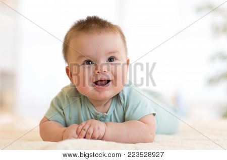 cute caucasian baby boy lies smiling on bed