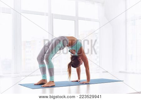 Beautiful woman practices backbend yoga asana Urdhva Dhanurasana - Upward facing bow pose at the bright yoga class with large windows