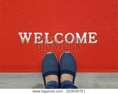 red welcome carpet with foot-ware on it