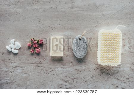top view of stones, dried roses, natural soap, pumice and bath sponge for spa on marble surface