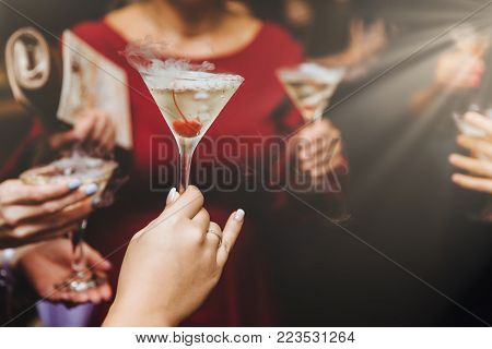 Cropped shot of unrecognizable females drink alcoholic cocktails, spend free time at night club, celebrate something. Alcoholic beverage in women`s hands. Friends clink glasses with cocktail