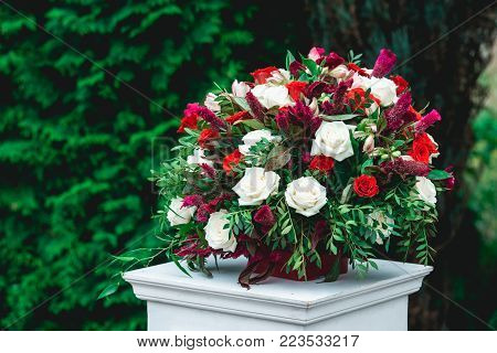 Wedding ceremony. Column, decorated with bouquet of red and white roses, in the wedding ceremony area. Trees on a background