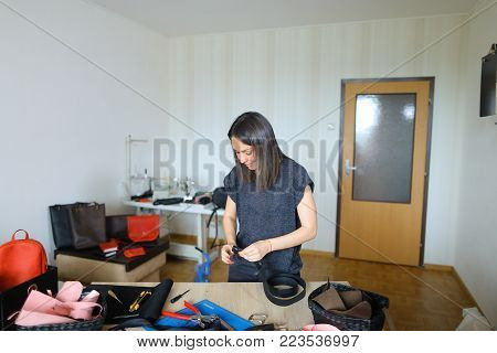 Female making black leather women bag. Girl likes handicraft and attending sewing circle. Lady with red manicure sitting near table with different instruments at workshop and fixing snap on pattern. Concept of hobby, leather products or handicraft.