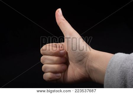 Young hand with thumb up  on black background