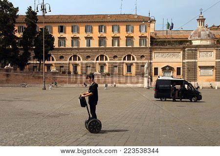 Rome, Italy - APRIL 12, 2016: The guy crosses the square on the segway.  People's Square (Piazza del Popolo) with its fountain and obelisk in centre named after the church of Santa Maria del Popolo - is a large urban square in Rome.