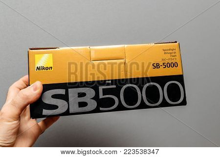 PARIS, FRANCE - JAN 23, 2018: Man holding against gray background a box of Nikon SB-5000 Speedlight featuring Radio Control Advanced Wireless Lighting, Cooling System