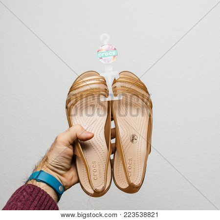 PARIS, FRANCE - JAN 23, 2018: Man holding a pair of new female shoes by Crocs Isabella Sandal bought online