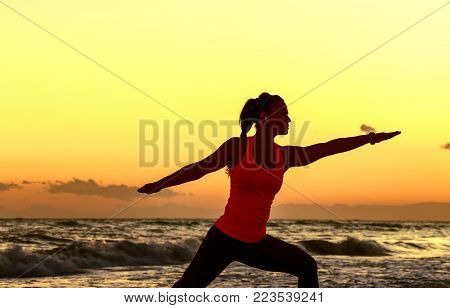 Silhouette Of Fit Woman In Sport Clothes On Beach Stretching