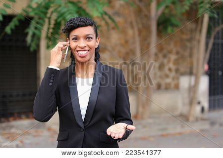 fiancee talking with truelove on smartphone in park with close up of beautiful face. Young girl has brown eyes, dark hair and heartfelt smile. Concept of new technologies and advantageous tariff plan for sharing genuine feelings.