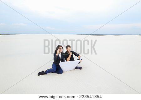 translators wife and husband move to alien city, married couple planning house at seaside. Young bearded fellow and fair-haired girl in glasses sitting on sand with whatman paper. Concept of exploring new territories, plots of land for sale or modern clot