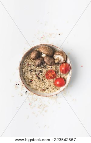 top view of raw rice in bowl with mushrooms and tomatoes on white surface with spilled rice and spices around