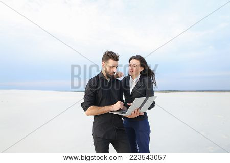 Journalists man and woman use laptop, colleagues preparing reportage about sailing competitions at coast. Bearded fellow and pretty girl with long hair standing among sands discussing work. Concept of innovative technologies, gadgets or business outfits.