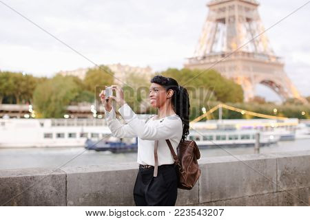 Lady standing on embankment not far from Eiffel Tower in Paris and watching pictures of landmarks made during day on mobile. Girl came to France to visit pen pal and decided to go on city tour. Pretty black-haired woman with beautiful hair styling wearing