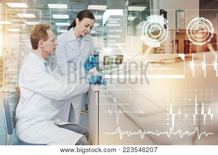 Scrupulous work. Calm attentive doctor holding a test tube with blood sample and his attentive cheerful coworker standing by his side and looking at it