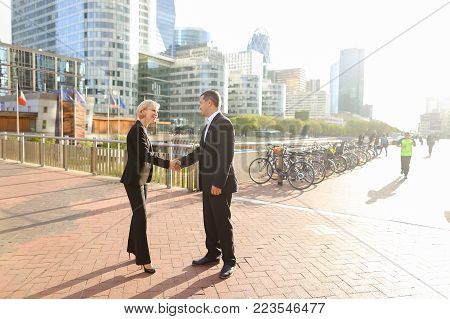 Male financial manager talking with employees outdoors. Concept of conversation with boss and decision making. Man in dark suit speaking with team members.