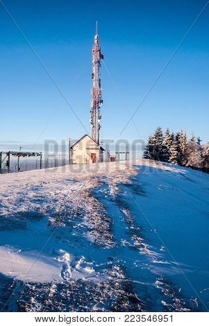 Ochodzita hill with transmitter above Koniakow village in Silesian Beskids mountains in Poland during winter morning with clear sky