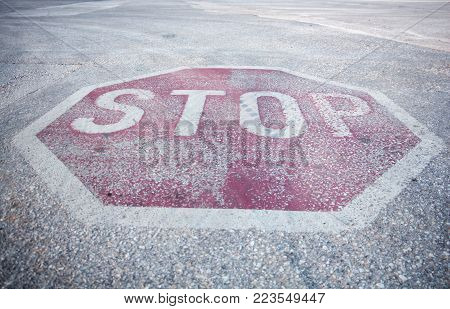 Weathered Red Hexagon Stop Sign Painted On Roads Pavement Surface, Closeup Background.