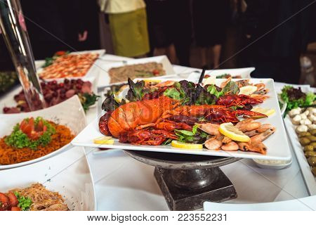 Fine selection of crustacean for dinner. Lobster, crab and jumbo shrimp on a white plate.