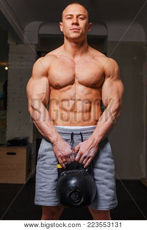 Strong muscular man bodybuilder shows his muscles holding kettlebell