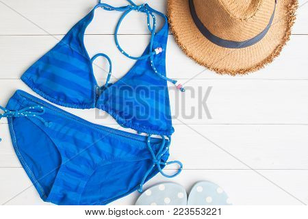 Bikini, straw hat and sandals on white wooden floor, Top view, Travel and vacation concept