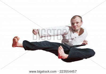 He strong and jumpy. Fighter jumping with foot kick in dojo