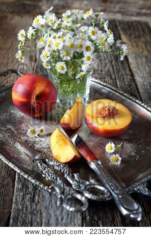 Summer composition. Bouquet of field daisies and ripe nectarines on vintage tray
